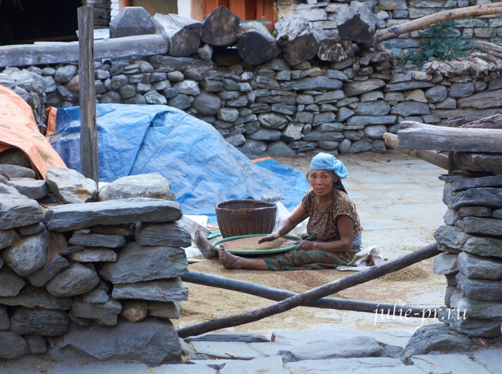 Непал, Трек вокруг Аннапурны, деревня Дана, женщина просеивает зёрна